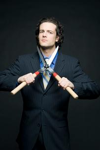 刈り込みバサミで首を切ろうとするビジネスマンの写真素材 [FYI03955193]