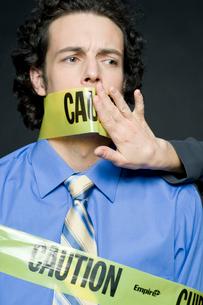 注意と書かれたテープで口を塞がれるビジネスマンの写真素材 [FYI03955198]
