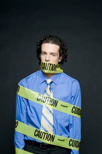 注意と書かれたテープで巻き付けられる男性の写真素材 [FYI03955201]