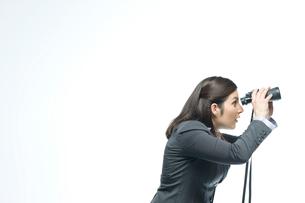 双眼鏡で遠くを眺めるビジネスウーマンの写真素材 [FYI03955202]