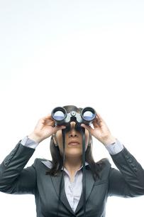 双眼鏡で遠くを眺めるビジネスウーマンの写真素材 [FYI03955205]