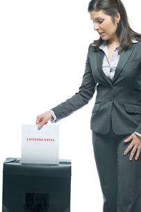 機密書類をシュレッダーにかけるビジネスウーマンの写真素材 [FYI03955208]