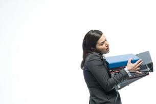 大量のファイルを両手で抱えるビジネスウーマンの写真素材 [FYI03955212]