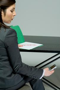 機密情報を携帯メールで送信するビジネスウーマンの写真素材 [FYI03955223]
