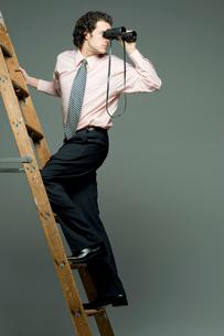 梯子に登りながら双眼鏡で遠くを眺める男性の写真素材 [FYI03955225]
