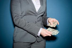 紙幣を数えるビジネスウーマンの写真素材 [FYI03955228]