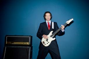 舌を出してギターを弾くビジネスマンの写真素材 [FYI03955230]