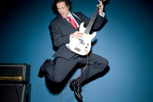 ギターを弾きながらジャンプするビジネスマンの写真素材 [FYI03955231]