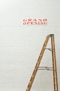壁に貼られた開店ポスターと梯子の写真素材 [FYI03955232]