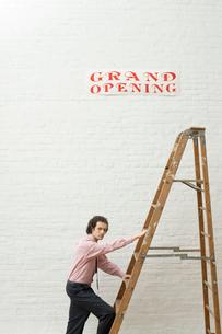 壁に貼られた開店ポスターと梯子に登る男性の写真素材 [FYI03955233]