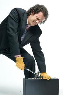 アタッシェケースをこじ開けようとするビジネスマンの写真素材 [FYI03955235]