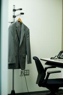 オフィスのハンガーラックに掛けられたスーツの写真素材 [FYI03955242]