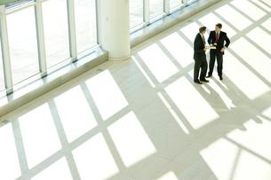 オフィスの通路で話し合うビジネスマンの写真素材 [FYI03955243]