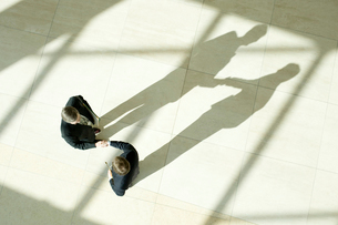 オフィスの通路で握手をするビジネスマンの写真素材 [FYI03955246]