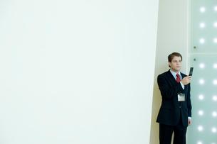 オフィスで携帯カメラで写真をとるビジネスマンの写真素材 [FYI03955255]