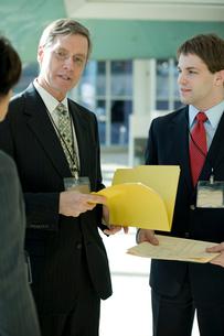 オフィスで立ちながら書類を確認するビジネスマンの写真素材 [FYI03955256]