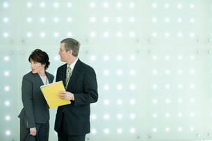 周囲を気にしながら書類を確認するビジネスマンの写真素材 [FYI03955257]