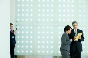 オフィスの男女社員を背後から盗撮するビジネスマンの写真素材 [FYI03955261]