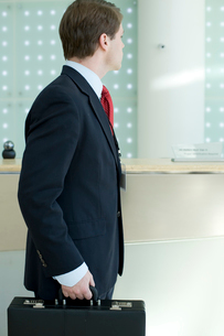 オフィスのセキュリティカメラの前を歩くビジネスマンの写真素材 [FYI03955262]