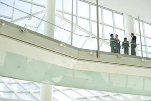 オフィスビルで立ち話をするスーツ姿の男女の写真素材 [FYI03955264]