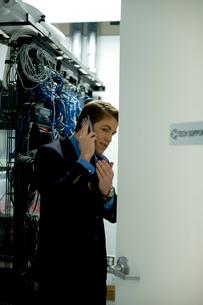サーバールームで携帯電話で話すビジネスマンの写真素材 [FYI03955280]