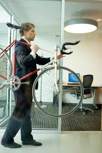 オフィスに自転車を運び入れるビジネスマンの写真素材 [FYI03955292]