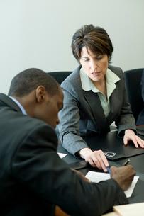 会議室で書類のやり取りをするスーツ姿の男女の写真素材 [FYI03955294]