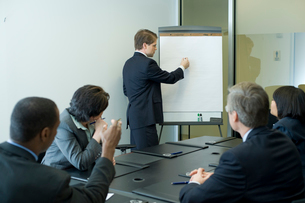 会議室でプレゼンテーションをするビジネスマンの写真素材 [FYI03955295]