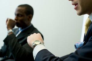 腕時計を眺めるビジネスマンの写真素材 [FYI03955298]