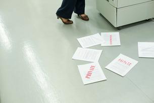 機密書類を床に落とすビジネスウーマンの写真素材 [FYI03955308]