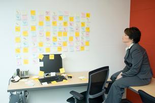 壁一面に貼られたメモを見つめるビジネスウーマンの写真素材 [FYI03955321]