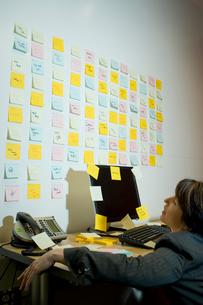 壁一面に貼られたメモをみてうな垂れる女性の写真素材 [FYI03955322]