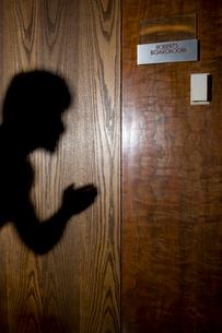 オフィスの前で盗聴するビジネスウーマンの影の写真素材 [FYI03955345]