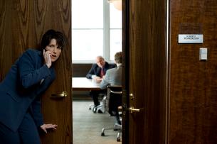 オフィスの前で盗聴するビジネスウーマンの写真素材 [FYI03955347]