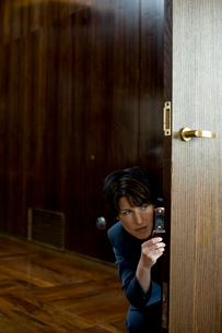 オフィスの前で盗撮をするビジネスウーマンの写真素材 [FYI03955348]