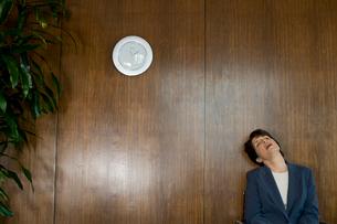 壁にもたれるビジネスウーマンの写真素材 [FYI03955350]