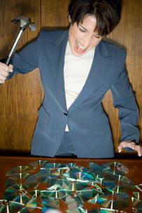 CDを金づちで割るビジネスウーマンの写真素材 [FYI03955352]