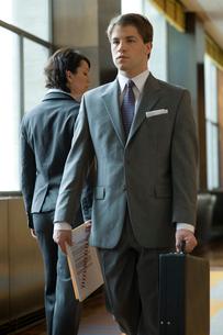 機密書類を手渡しするスーツ姿の男女の写真素材 [FYI03955354]