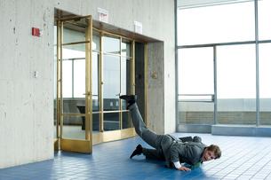 オフィスの入口で床に転ぶビジネスマンの写真素材 [FYI03955356]
