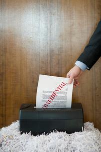 機密書類をシュレッダーにかけるビジネスマンの写真素材 [FYI03955364]
