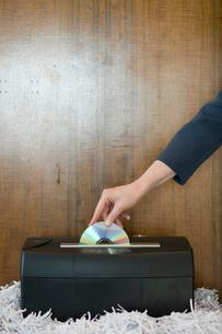 機密CDをシュレッダーにかけるビジネスマンの写真素材 [FYI03955365]