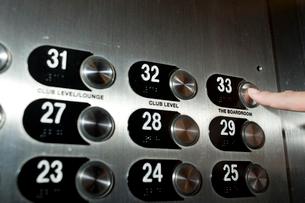 エレベータボタンを押すビジネスマンの指の写真素材 [FYI03955366]
