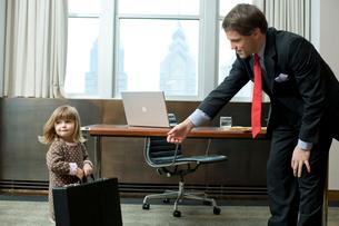 オフィスで父親の鞄を運ぶ娘の写真素材 [FYI03955367]