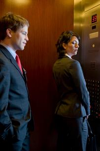 エレベーターで女性を見つめるビジネスマンの写真素材 [FYI03955368]