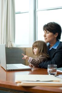 オフィスでパソコンを見つめる母親と娘の写真素材 [FYI03955369]