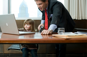父親のオフィスのパソコンで遊ぶ娘の写真素材 [FYI03955370]