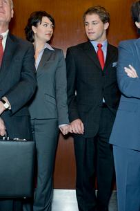 エレベータで手を繋ぐスーツ姿の男女の写真素材 [FYI03955372]