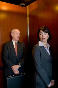 エレベーターで女性を見つめるビジネスマンの写真素材 [FYI03955373]
