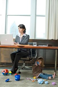 オフィスで働く女性と床で遊ぶ娘の写真素材 [FYI03955375]