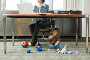 オフィスで働く女性と床で遊ぶ娘の写真素材 [FYI03955377]